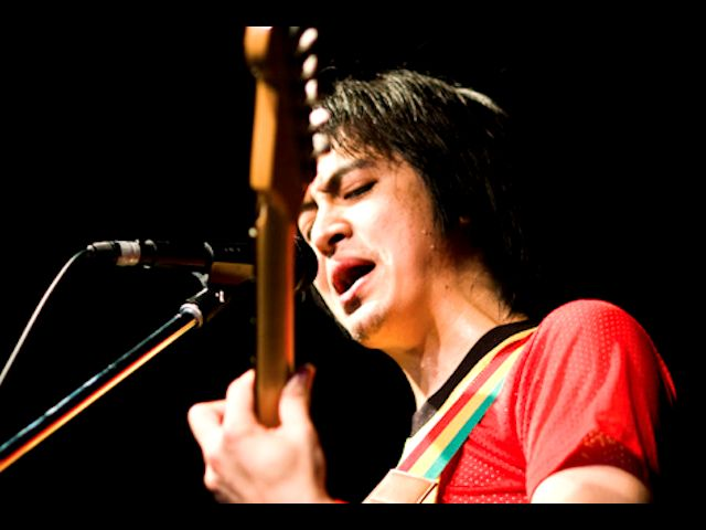 ギターを弾く赤い服の人