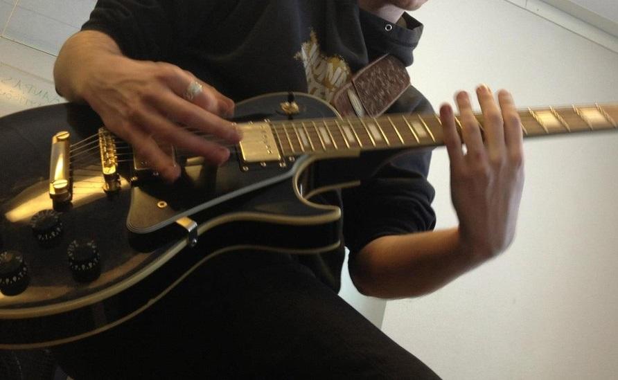 黒いいギターを弾く男性