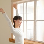 窓際で伸びをする女性