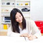 机で書きものをする女性