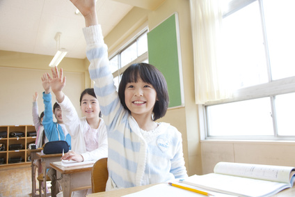 授業中に手を挙げる小学生男女