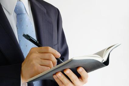 手帳に記入するビジネスマン