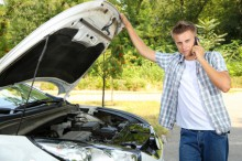 Man calling repair service after car breakdown
