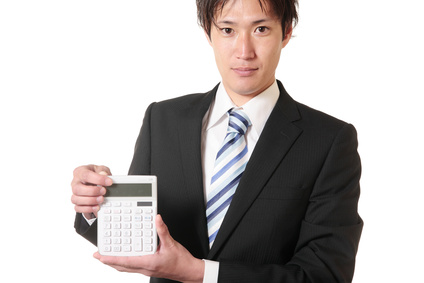 電卓を持っているスーツの男性