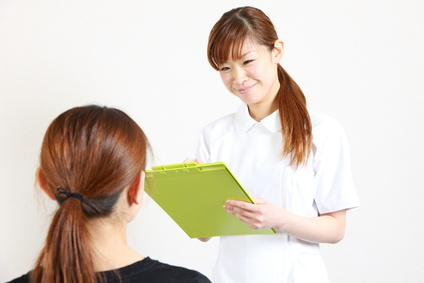 young japanese nurse talks with patient