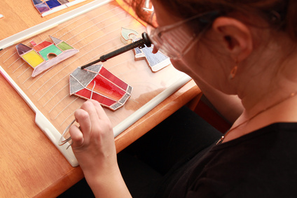 Stained glass maker works with colorful souvenirs