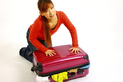 スーツケースが閉まらない女性