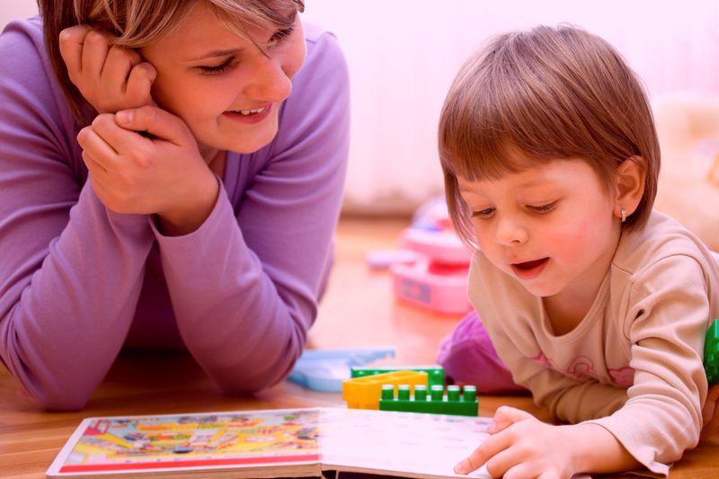 絵本を見る指導者と子供