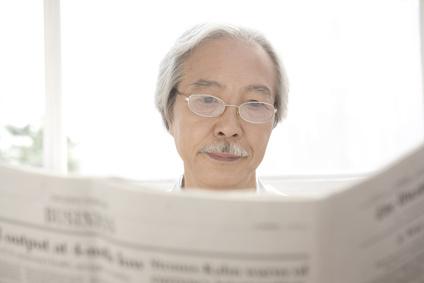 新聞を読む初老の男性