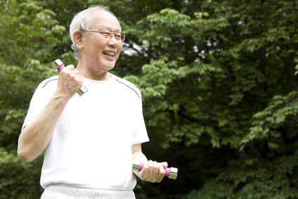 公園でダンベルを持ち筋トレしている老人