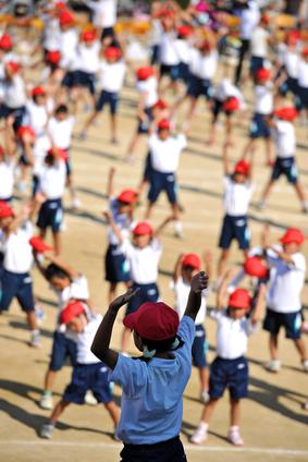 小学校の校庭でラジオ体操をする子供たち