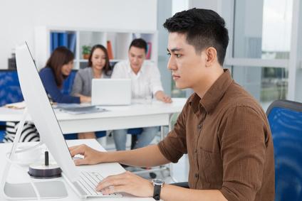 パソコンに向かう東南アジアの人
