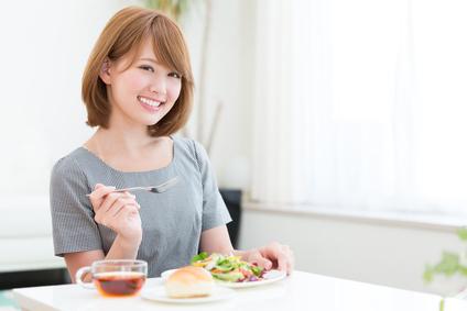 朝食にサラダを食べる女性