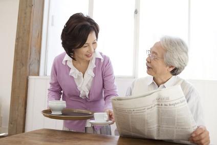 新聞を読む初老の男性とお茶を入れる妻