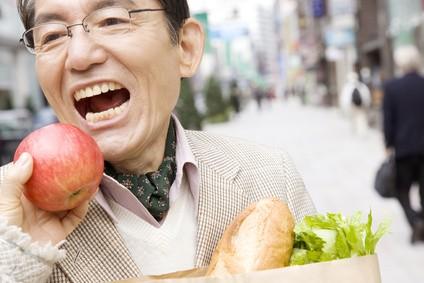 りんごに齧りつく男性