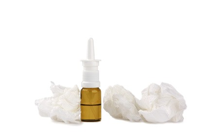 Nasal spray and used tissues. Cold and flu or allergy concept