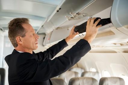 機内で手荷物を棚に乗せるビジネスマン