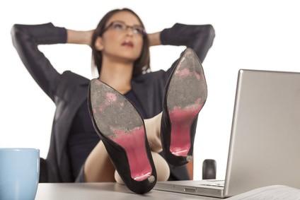 机に脚を乗せて仕事をさぼる女性